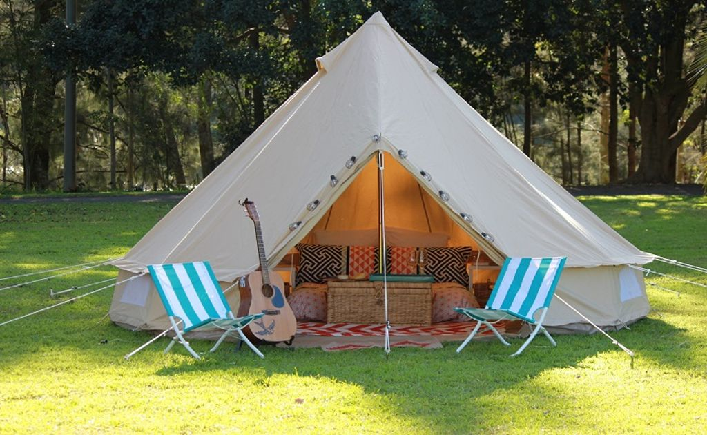 Looking for glamping tents for sale? Australia has plenty of rentals like this, with blue striped deck chairs and guitar