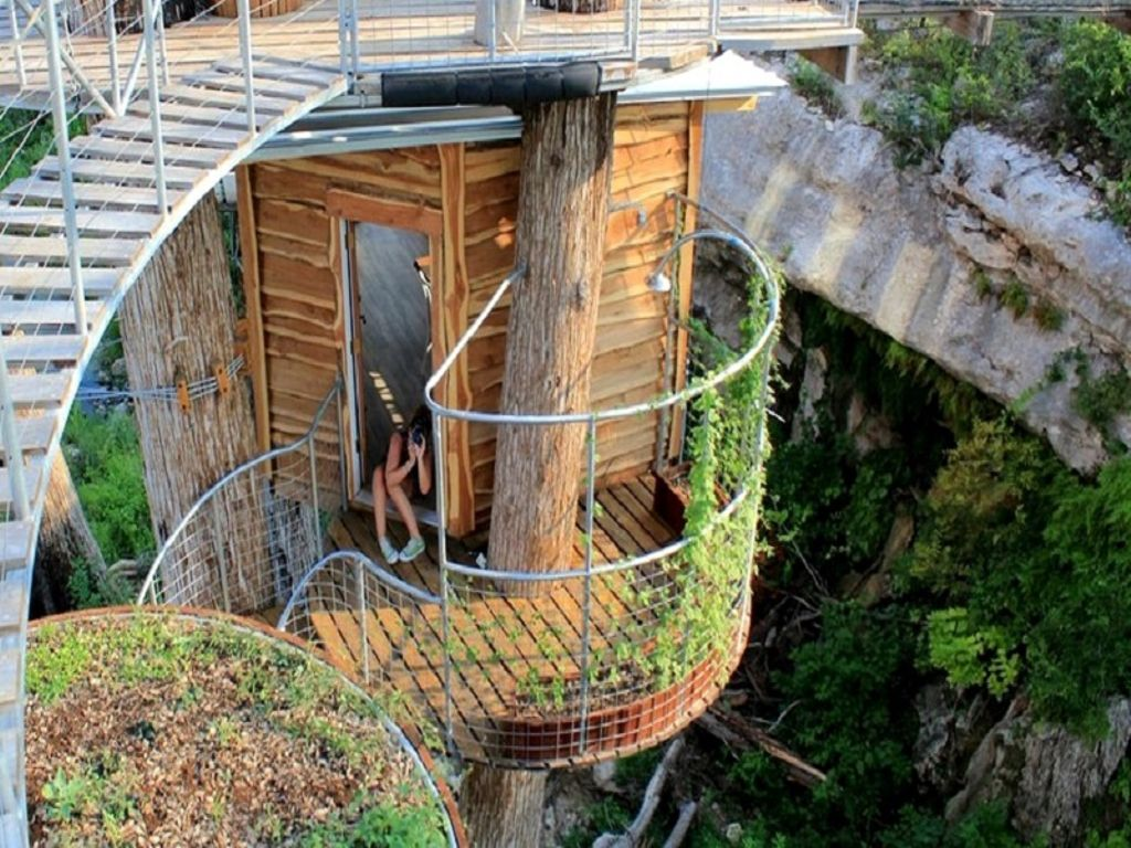view of woman on treehouse rentals in texas for family friendly getaways, at one of the top unique home rentals