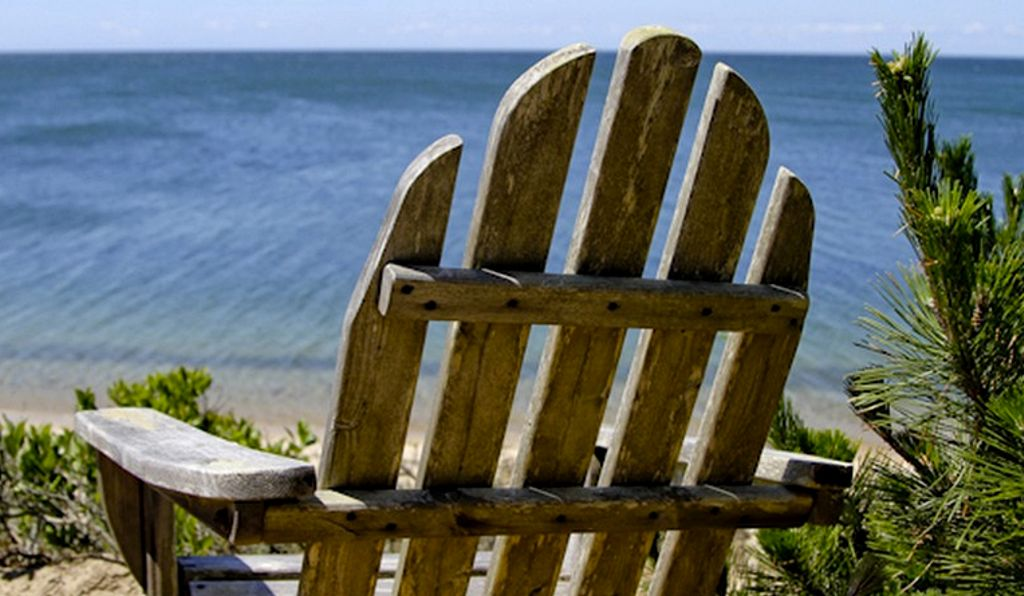 An Adirondack chair looking out over a Cape Cod beach as a stop on an East Coast road trip.