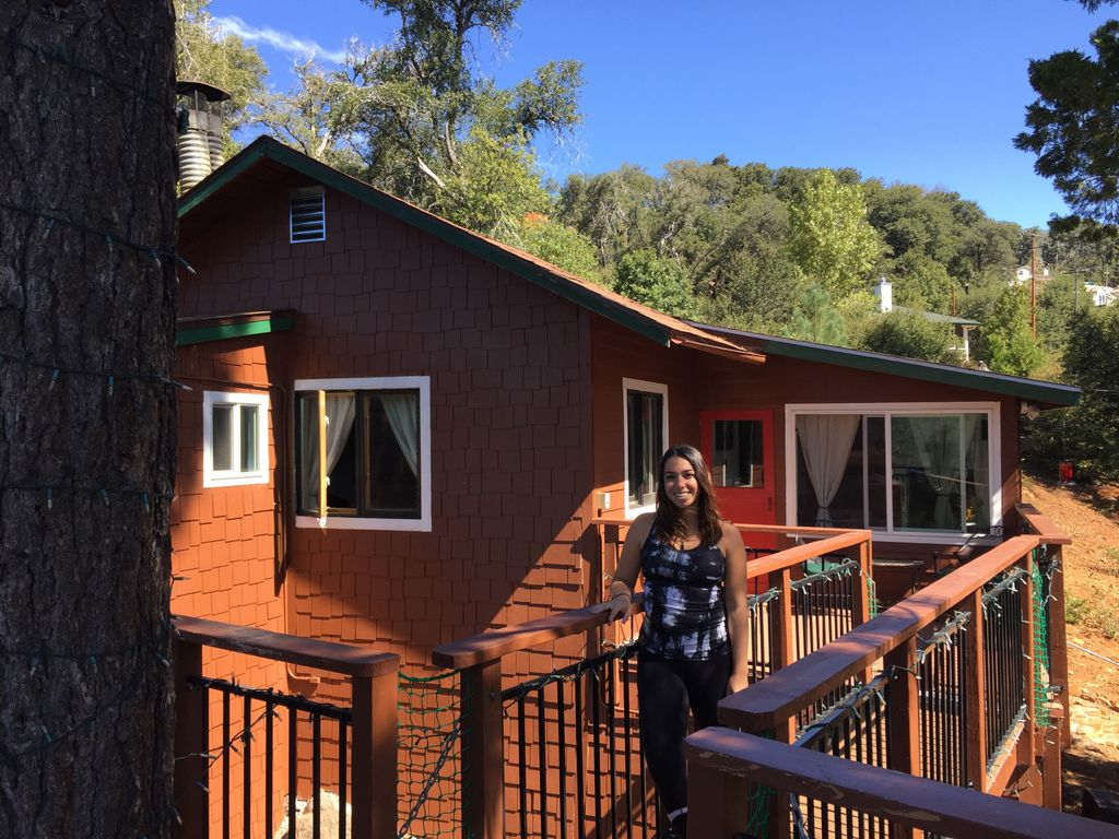 A photo of the author in front of the tree house California during visit-Julian experience.