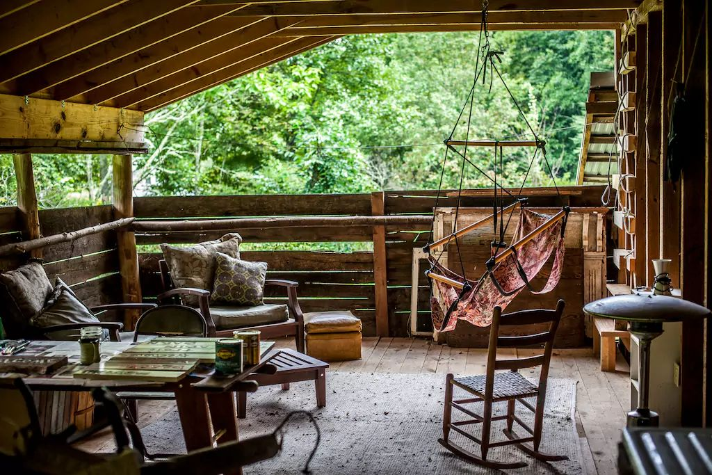 A view of the cozy porch area, complete with outdoor furniture for relaxing and soaking up the woodland views.