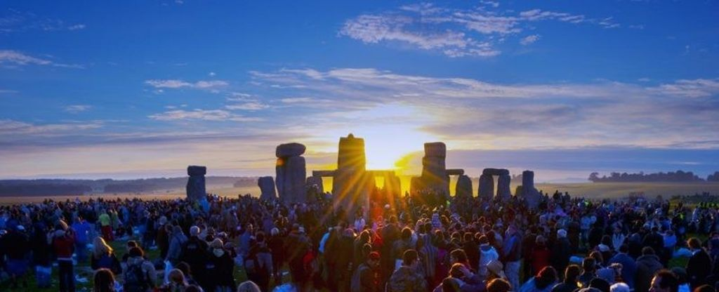 a crowd gathered at the Stonehenge summer solstice