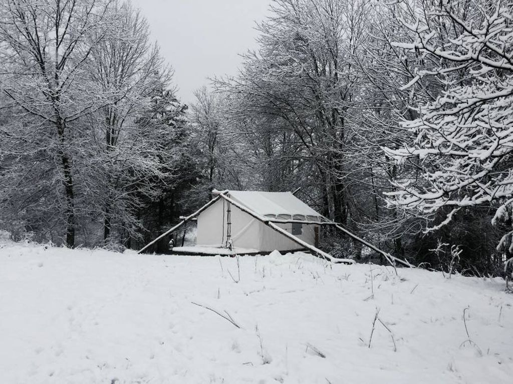 A tented cabin in the woods of Upstate New York, covered in snow.