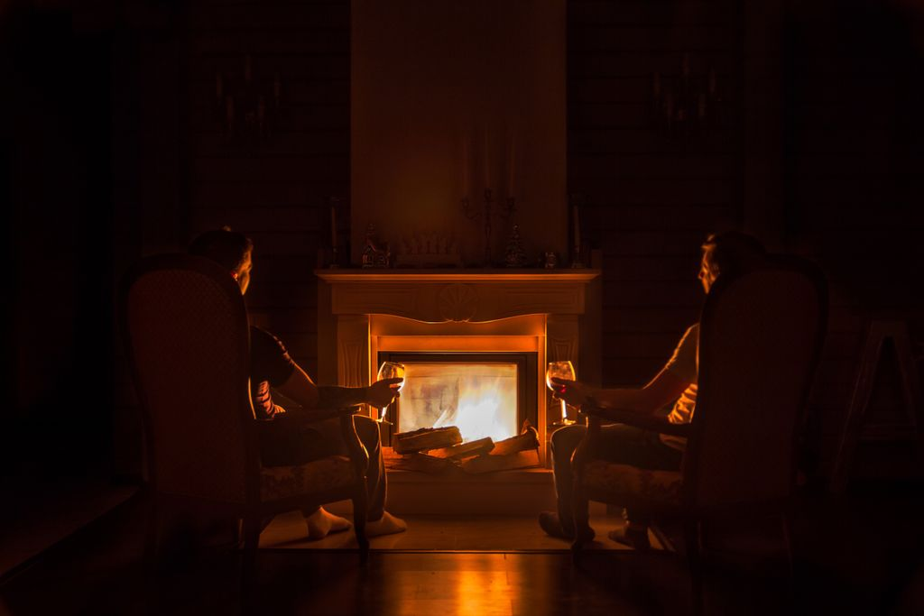Two people sitting in arm chairs with a glass of wine at night in front of a fireplace.