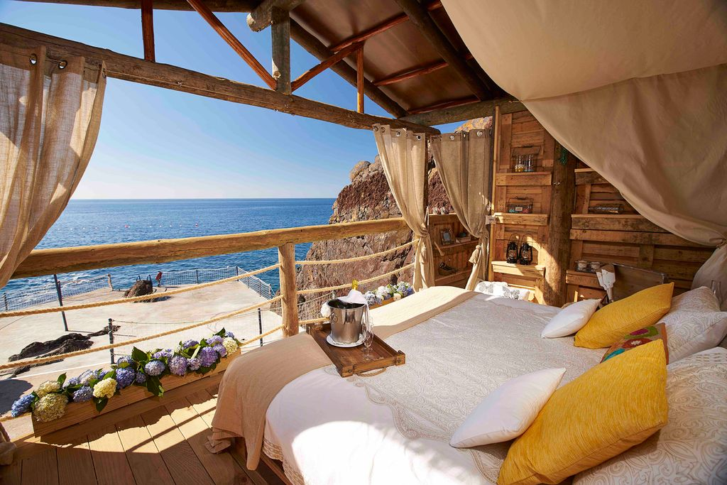 A plush double bed in front of an open wall overlooking the ocean