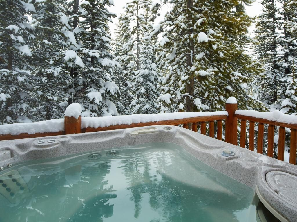 Hot tub on a deck surrounded by trees covered in snow.