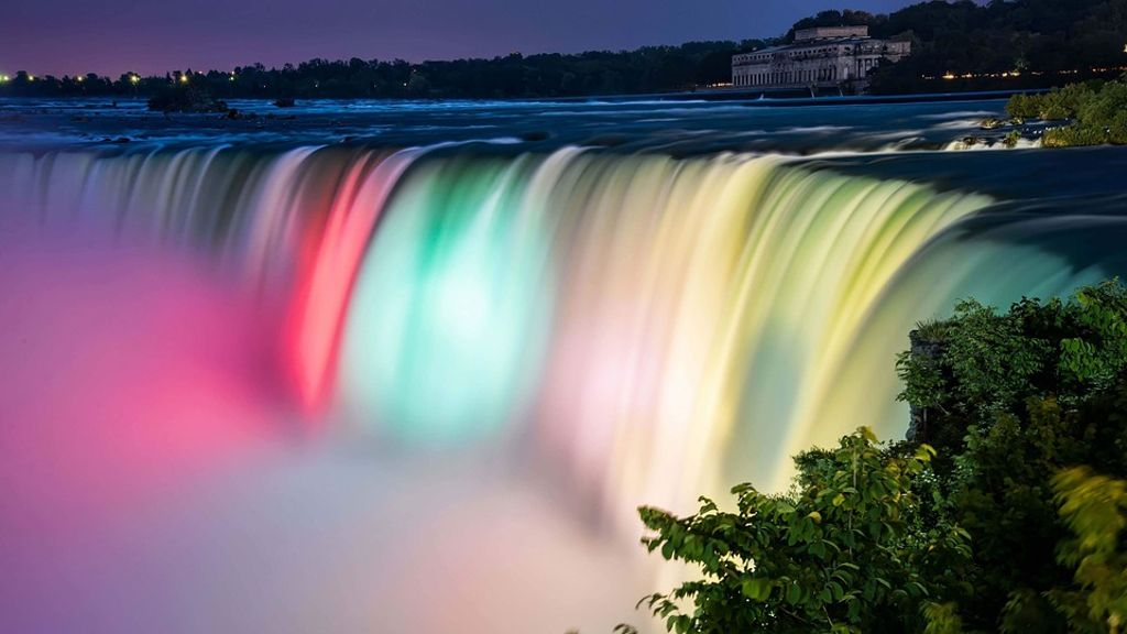 The Niagara Falls lit up with multi colored lights