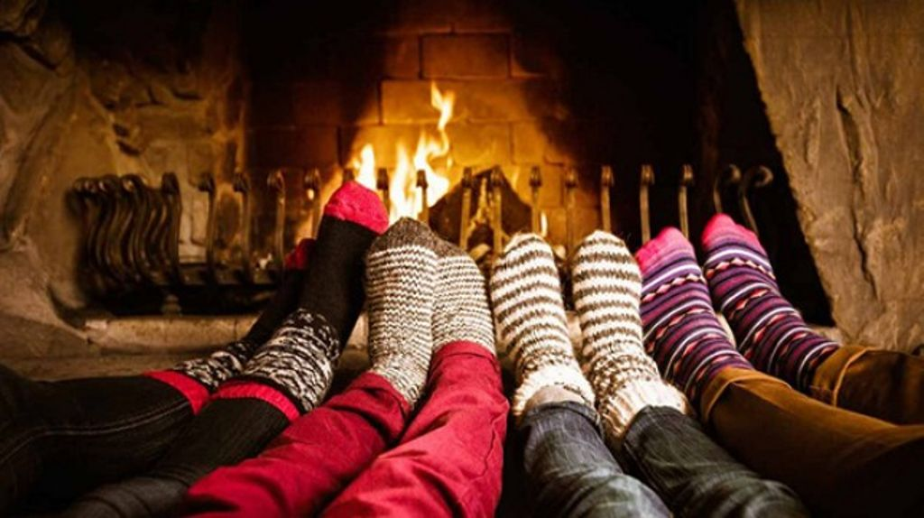 Hosting Christmas by the fire with warm festive socks in shot