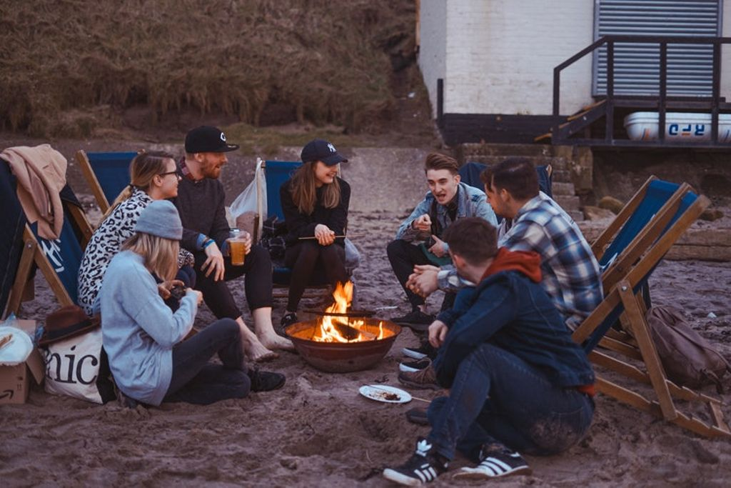 group enjoying fire pit and one of the best glamping essentials and travel gadgets around