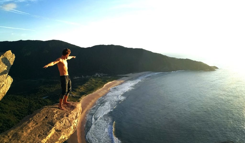 A glamper standing on top of a cliff overlooking the unspoiled coastline below