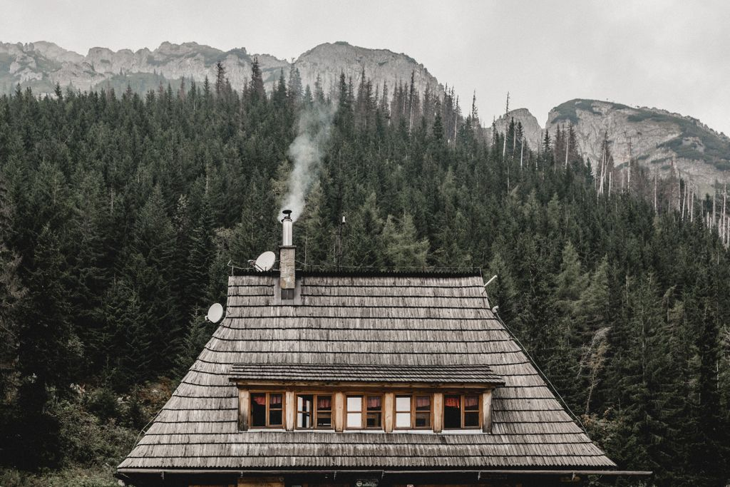 Smoke leaving the chimeny of a mountain cabin rental surrounded by pine trees for a winter camping vacation.