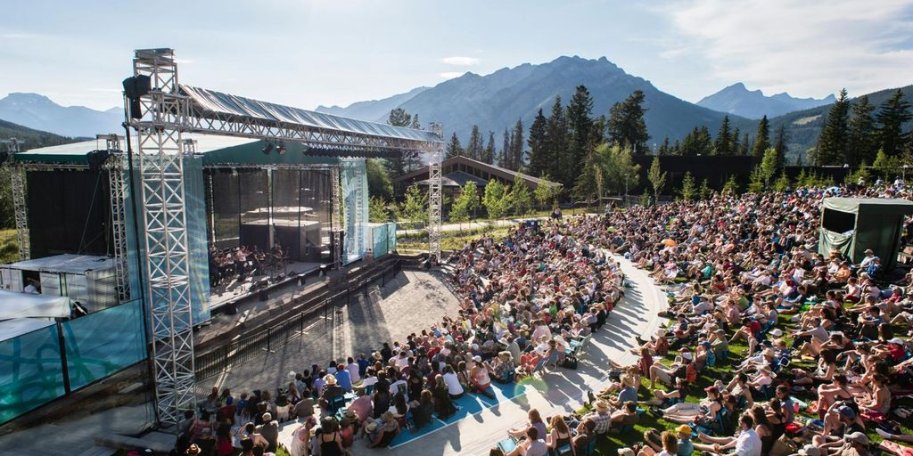 People sat enjoying Banff music concert, part of the Banff National Park guide with upcoming events and more