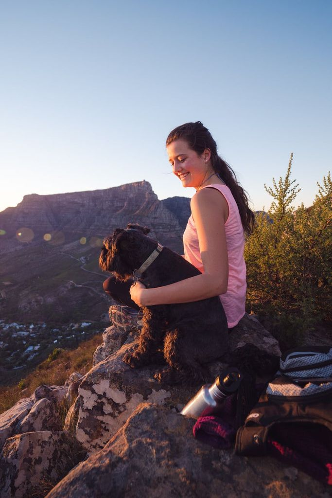 woman sat during her camping trip in the wilderness with dog on dog hiking trail