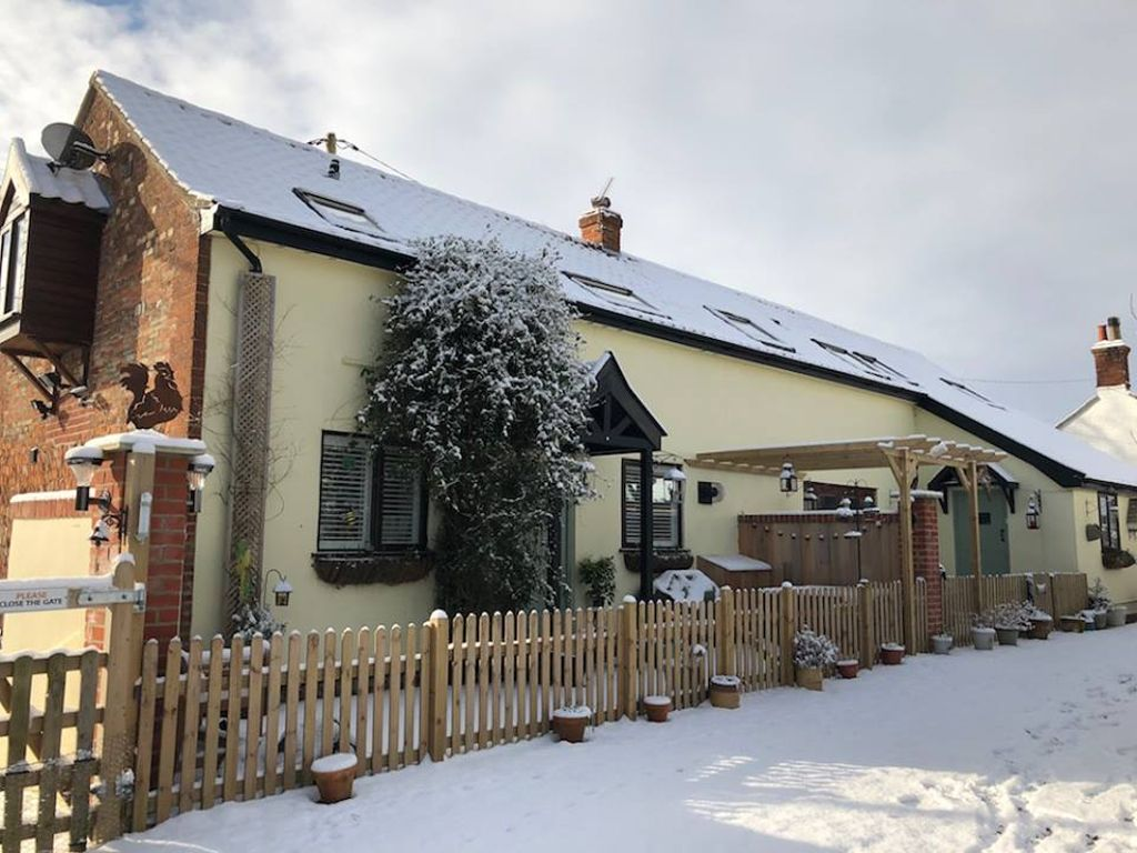 The outside of winter cottage UK with brown picket fence and snow upon rental and outside.