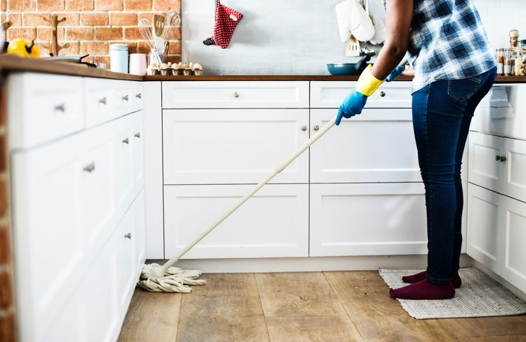 woman tidying kitchen after learning how to keep house clean in 2020