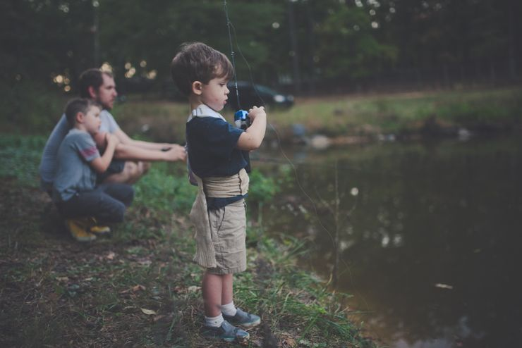 young boy next to father fishing as part of best father's day gift ideas