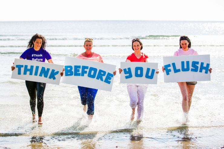 four women stand in the ocean, to make a point on how to clean up beaches